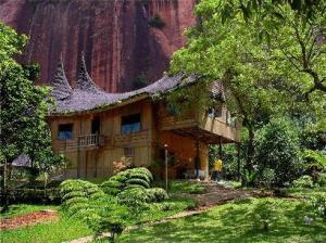 """Resort dengan arsitektur rumah """"bagonjong"""" khas Minangkabau berada tepat di bawah tebing curam."""